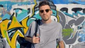 grafiti : Graffiti artist is walking away from a graffiti wall with a backpack on his shoulders