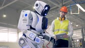 droid : A male worker switches on a robot to start a work.
