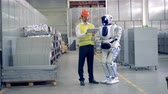 droid : A factory worker shows a robot what to do at industrial factory. Stock Footage