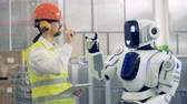 droid : White robot copies mans gestures at a warehouse, then gives him a hi-five. 4K.