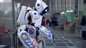 emulator : Human-like robot is working with a drill in a factory unit Stock Footage