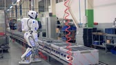 emulator : Human-like robot is getting switched on and allowed to start drilling by a factory worker