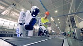 emulator : Factory worker is regulating robots settings by remote control during working process
