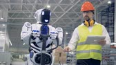 emulator : Cyborg is moving a transporting tool along the factory unit while being regulated by a male worker Stock Footage
