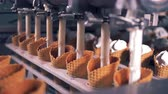 wafers : Tubes are pumping creamy substance into lines of wafer cones