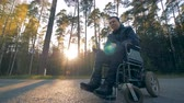 реабилитация : One man sits in a black wheelchair. Стоковые видеозаписи