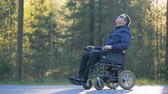 гандикап : A person in glasses sits in a wheelchair.