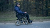 dependência : Man in a wheelchair enjoys nature, side view.