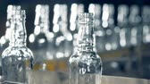 ремень : Ribbed necks of glass bottlings moving along the transporter in a close up