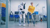 futurism : Young woman is dancing with a robot who spanks her playfully after whereafter she leaves
