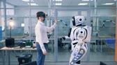 five : A man in virtual glasses and a robot are giving each other high-five Stock Footage