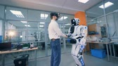 интерес : An adult man in virtual glasses is shaking robots hand and turning around