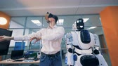 industrial revolution : Male engineer is standing next to a cyborg and manipulating virtual reality through glasses