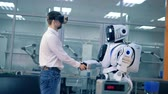 advance : A human and a human-like android are shaking hands and watching virtual reality