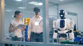 buluş : Human-like robot is copying moves of a male lab worker under supervision Stok Video