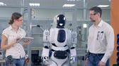 droid : Engineers walk together with a robot.