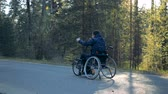 cadeira de rodas : Training wheelchair is getting moved along the road by a disabled man Stock Footage