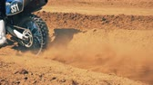 riders : Motorbike is getting started by the rider in a dusty terrain. Stock Footage