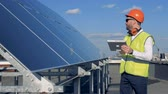 transforming : Solar panels is getting checked by a male expert in workwear