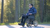 závislost : Disabled man in a powered wheelchair is sitting against the background of a forest