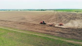 farming equipment : Plowing tractor rides on a big field, top view.