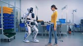 wynalazek : A woman meets a robot in a room. Robot and woman give each other a high-five, then a droid copies her movements with fingers.