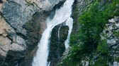 érintetlen : Natural waterfall in the mountains. Tall waterfall in the mountains is streaming down. Stock mozgókép
