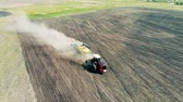 arando : Agricultural tractor is sowing ground in a cloud of dust. Vídeos
