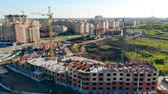 urban development : Building process on a construction site. Cranes build new houses on the city outskirts. Stock Footage