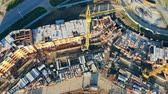urban development : Crane near unfinished building, top view. Construction crane builds a new brick house on a site.
