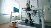 ferido : Modern medical recovery device. Training process of a physically challenged man on a walking simulation system