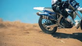 soutěž : Motorbike is being driven across an offroad terrain. Slow motion