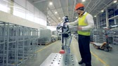 technik : A robot works at a warehouse with a human, close up. Dostupné videozáznamy