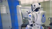 droid : Robot comes to a machine and types, back view. Stock Footage