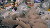likvidace : Piles of garbage move on a conveyor, close up. Lots of rubbish is on a moving line at a recycling plant.