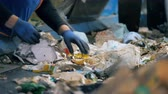 separating : Two workers sort garbage on a conveyor, close up. People work at a factory, sorting moving trash. Stock Footage