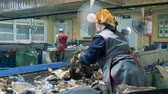 recycling facility : Women work at a plant, sorting garbage, close up.