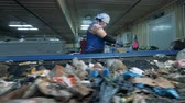 sorts : Woman checks garbage on a conveyor, close up. Worker sorts trash in a room at a factory.