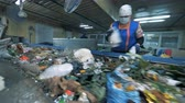 separating : Female factory employee is sorting waste for further recycling. Waste recycling plant. Stock Footage