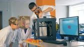 teach : Children and a school teacher work with a 3D printer in a laboratory, close up.