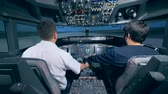 кокпит : Two men are sitting in a cockpit of a flight simulator. Cockpit cabin flight deck.