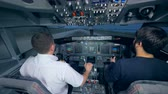 captain : Two men are practicing landing in a flight simulation machine Stock Footage