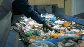aterro : Garbage recycling plant. A person in gloves picks unrecyclable trash from a moving line at a waste sorting factory.