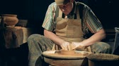 мастер : Pottery man creates a bowl. A person works at a pottery, making a clay bowl on a wheel. Стоковые видеозаписи