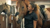 amazona : Professional athlete pats a horse in a stable. Human and animal love concept.