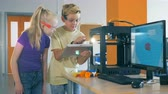 educação escolar : Course of 3D printing is getting controlled by two kids from a tablet computer
