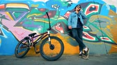 grafiti : Young stylish teenager biker talks on a phone outdoors. Active Teenager concept.