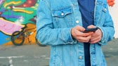 grafiti : Casual teenager typing text massage with a smartphone, close up. Dostupné videozáznamy