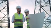 transformador : Two workers checking a scheme, close up.