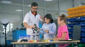 agitated : Engineering playroom with two teens and a male worker getting to know a toy robot